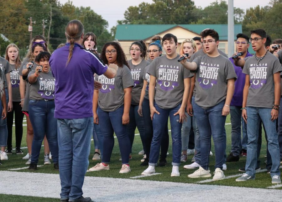 Members of the Wildkat choir under the direction of director Ken Labonski sing before the first football game on September 6, 2019. The choir is busy with TMEA auditions, the annual Short and Sweet concert on September 26th and practices for public performances like the football games.