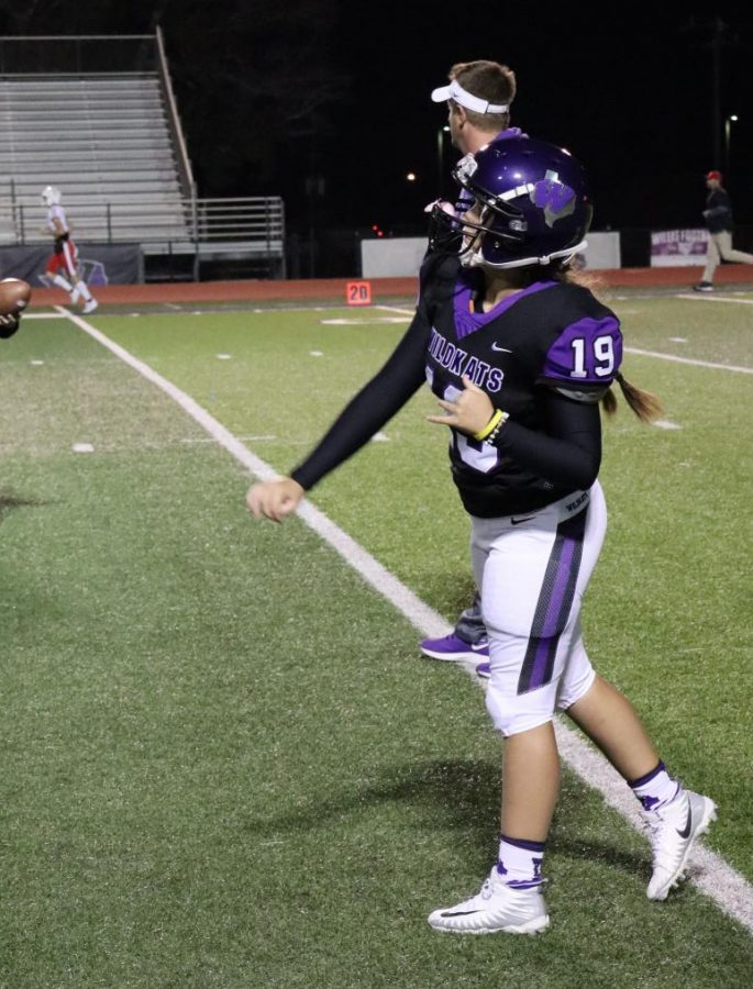 """ONE OF THE GUYS. Warming up before the game against Tomball, junior Emilee Buhl throws a pass to a teammate. Buhl made history on Friday by suiting up with the varsity. """"I plan on working extra hard to prepare for next season,"""" she said. """"I would love to play in a varsity game again."""""""
