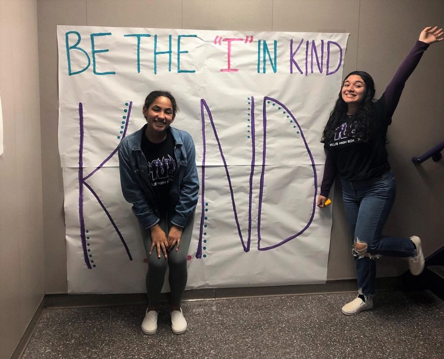 BE+THE+I+IN+KIND.+Sophomore+Maci+Konen+and+senior+Ocany+Flores+celebrate+kindness+week+with+a+sign+painted+by+Stuco.+