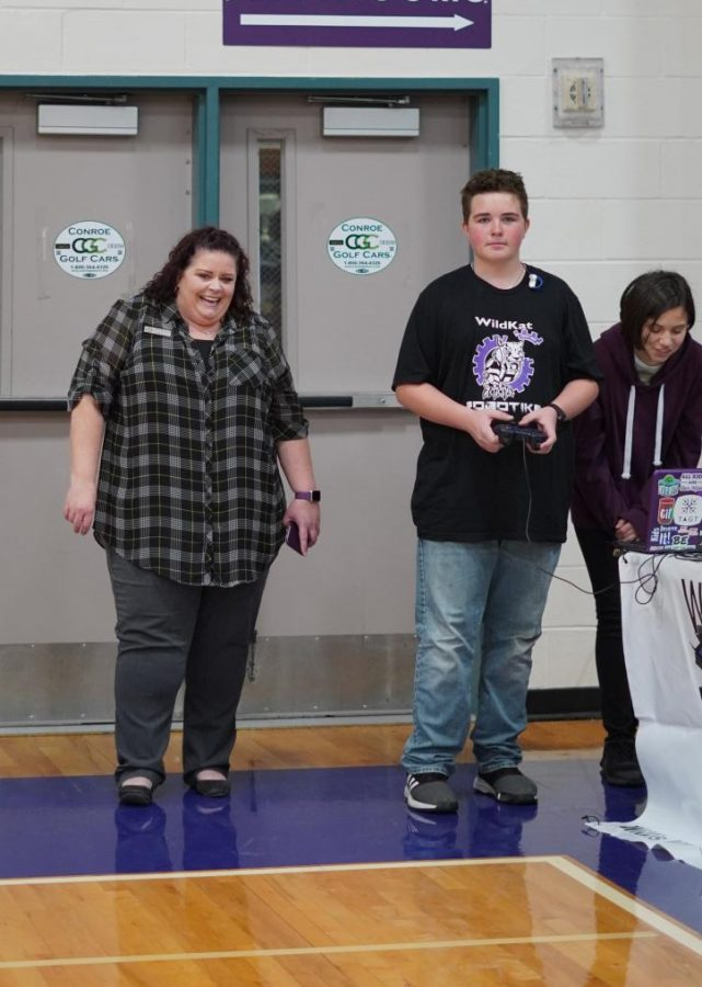 Moving the robot as 8th graders tour the gym, freshman James Rogers recruits new members for the Robotiks team during the 8th grade visits.