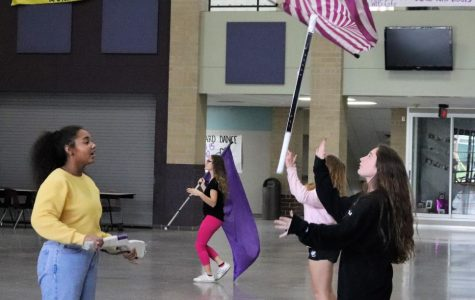 At after school practice, junior Kasey McGrew works on fundamentals with freshman Tory Pierce. The Winter Guard  practices after school and during their 7th period class.