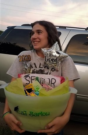 """With her present from a family friend, senior Cali Barlow accepts her gift of senior swag. Barlow was adopted by several families after her mom posted her information on the Facebook page Willis High School Adopt/Swap a Senior 2020.  """"The worst part is realizing that this chapter of my life is truly over,"""" Barlow said. """"Being 'adopted' made me realize that you never really lose the people who mean the most to you. They're in your heart forever."""""""