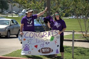 Wresting coach Bryan Thomas and English teacher Bridget Thomas cheer the senior on. Faculty members surprised seniors by celebrating the class of 2020 when they came to pick up their yard signs.  The event was meaningful to the teachers and students since the ending of the school robbed them the chance for traditional good-byes.