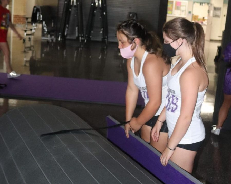 TEAMWORK MAKES THE DREAMWORK. Rolling out the mats for practice freshmen cheerleaders Skyler Horton anfd Kelsey Weddington spend their afternoon of their first day of high school at cheer practice. Even though school is remote, organizations like cheer are able to host practices if they follow safety protocol due to COVID-19.