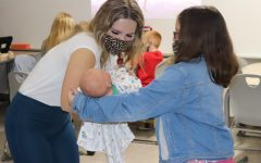ROCK A BYE BABY. Helping a student with a baby, senior Lindsay Davenport works with the Turner Troop. Members of the child guidance class works with the children of high school teachers and staff members before walking them to AR Turner.