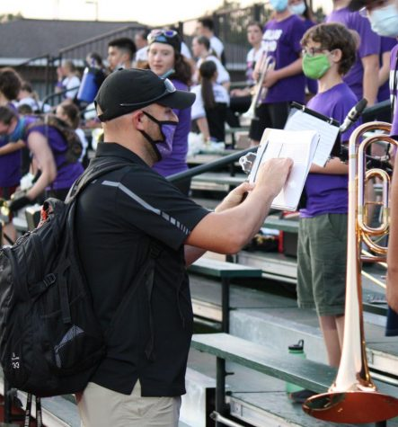 MAKING ADJUSTMENTS. Doing his best to keep band members at a safe distance, assistant band director Joseph Ditfurth sets the seating arrangement at Friday night
