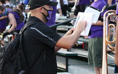 MAKING ADJUSTMENTS. Doing his best to keep band members at a safe distance, assistant band director Joseph Ditfurth sets the seating arrangement at Friday night's scrimmage against Cy Falls.