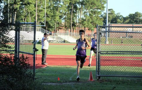 LEADERS OF THE PACK. At the race against Magnolia West, junior Kayman Hatthorn and Braden Kurtz lead the pack of runners from the track to the wooded section of the course.
