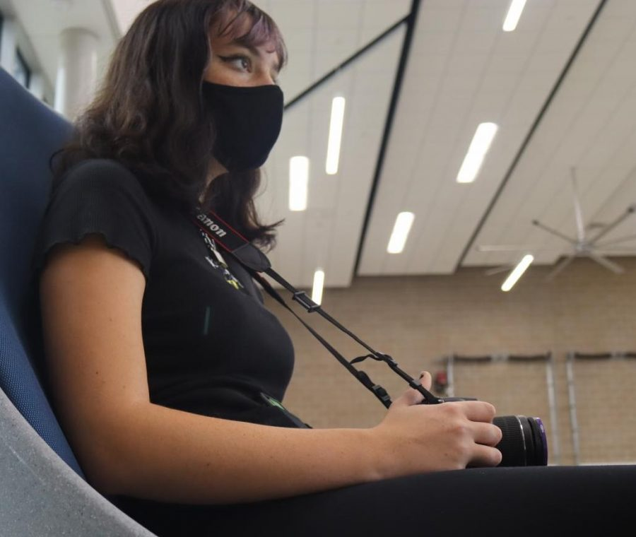 ALL MASKED UP.  Taking pictures in the CTE building, junior Madi Bagley wears a mask while completing her yearbook assignment.