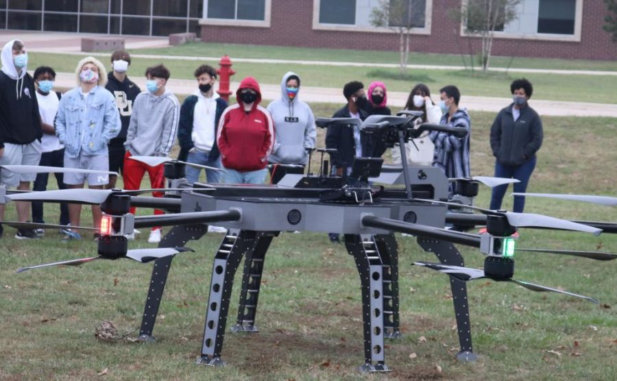 SEEING IS BELIEVING. Students crowd around the Scorpion drone during a morning demo.