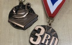SHOW ME THE BLING. Wilkdat journalist medaled at the Rough Riders Invitational.