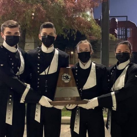 SWEEPSTAKES. After earning ones at district the drum majors, seniors Alex Hopkins, GianReo Mire, Melanie Merkley and Stephanie Orozco, celebrate with a picture with the Sweepstakes trophy.