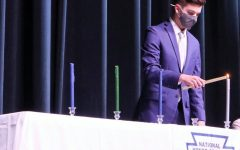 SCHOLARSHIP. Lighting a candle that symbolizes the pillar of scholarship,, senior GianReo Mire  NHS president, starts the officer portion of the induction.