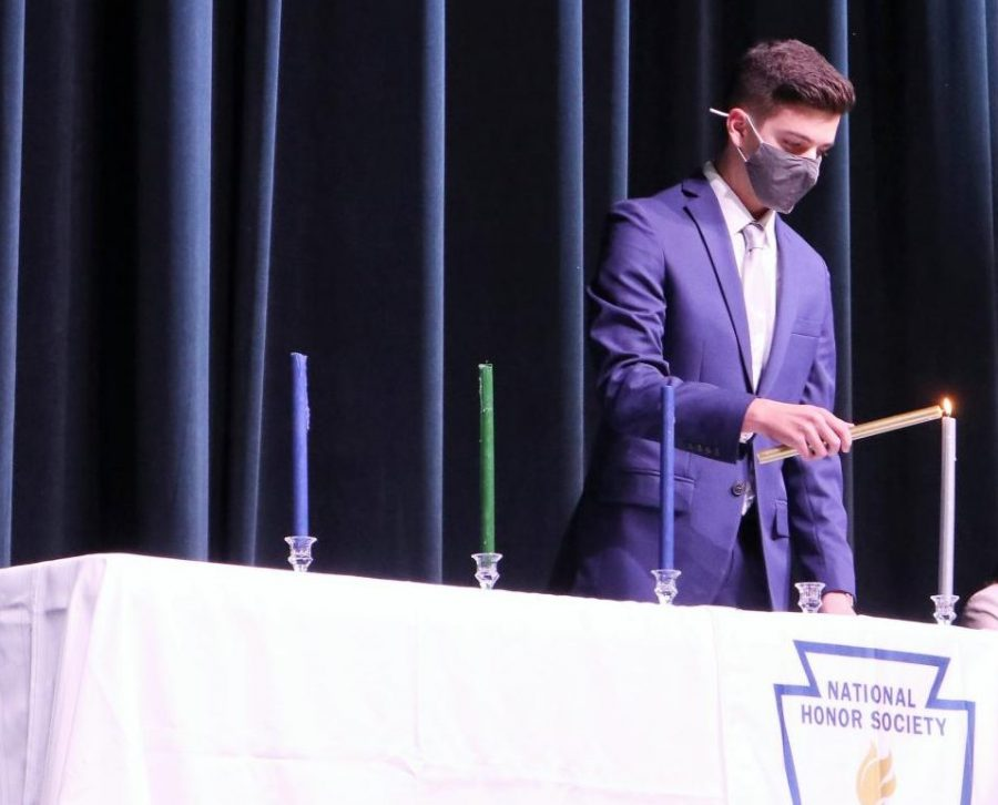 SCHOLARSHIP.+Lighting+a+candle+that+symbolizes+the+pillar+of+scholarship%2C%2C+senior+GianReo+Mire++NHS+president%2C+starts+the+officer+portion+of+the+induction.+