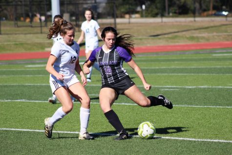 MAKING HER MOVE.  Preparing to send the ball closer to the goal, sophomore Lucy Smith readies to kick as a Lake Creek player approaches. Smith plays soccer for the school and is also on a club team.