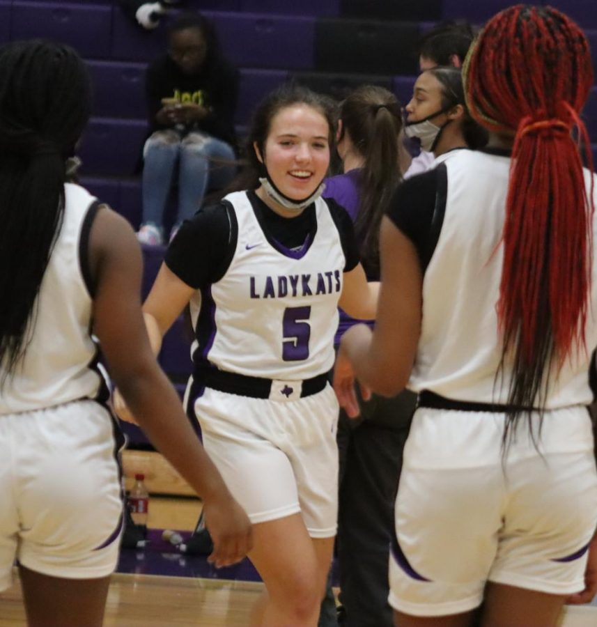 ALL SMILES ON COURT. Being intriced with the starting lineup, sophomore Lucy Smith enters the court. This is her second year to play varsity basketball.