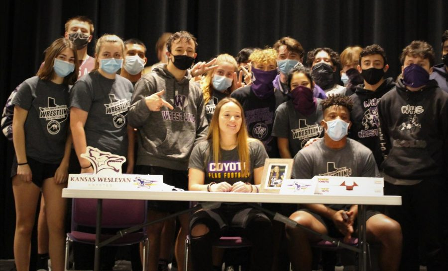 SUPPORTING+THEIR+OWN.++Members+of+the+wrestling+team+support+senior+Emilee+Buhl+sign+her+letter+of+intent+to+play+at+Kansas+Wesleyan+to+play+football.++