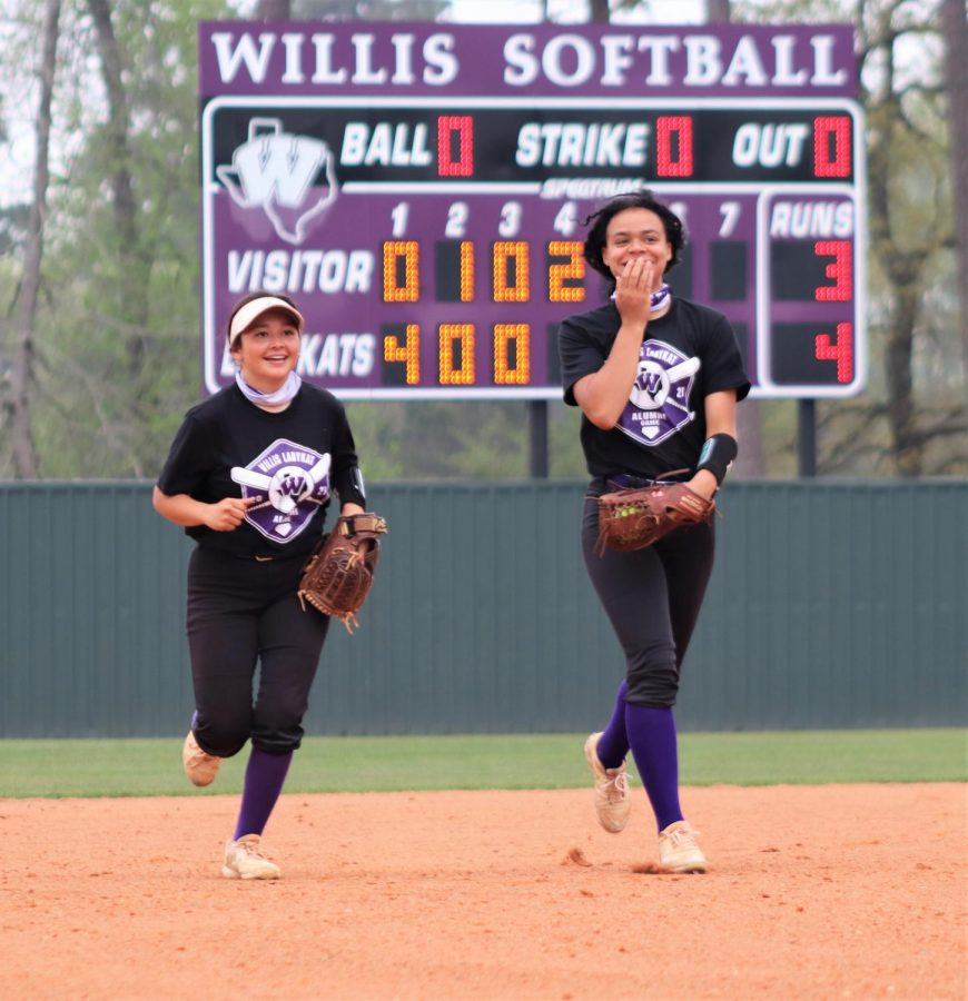 SHOCKED AND AMUSED. Surprised by the intensity of the alumni players, seniors Cynthia Moreno and Kaleyana Bankhead head back to the dugout from the outfield.
