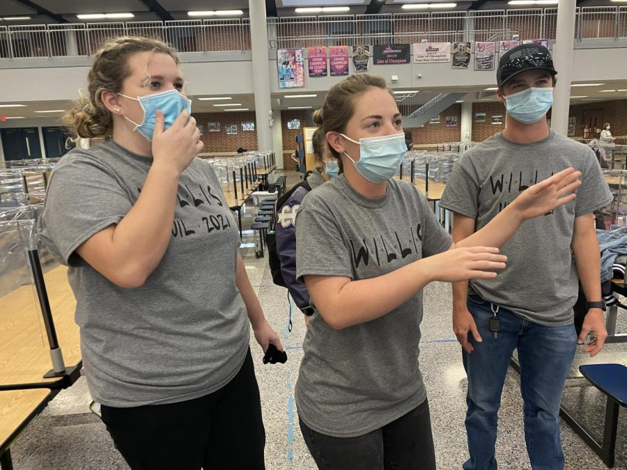 LISTEN TO ME. Passing the day away with games, juniors Katherine Lee, Heather Jackson and Brenan Mansker give clues in a games of Heads Up at regional UIL on Saturday, April 17.