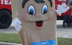 HERE EVERY IS BETTER. HEB Buddy waves at the cars as the teachers and staff drive through the HEB Texas Loves Teachers Tour.