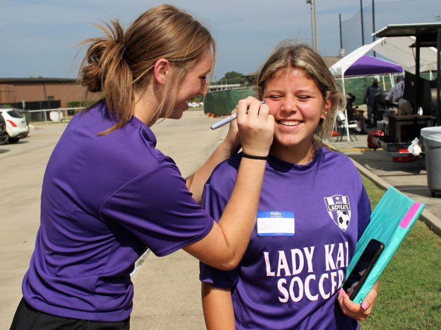 TAILGATING AND FUNDRAISING. Before the first home game against Tomball, sophomore Georgia Paugh decorates the cheek of freshman Saydi Wood with Wildkat spirit. The girls soccer and basketball teams held bake sales during the tailgating and game to raise money for their programs.