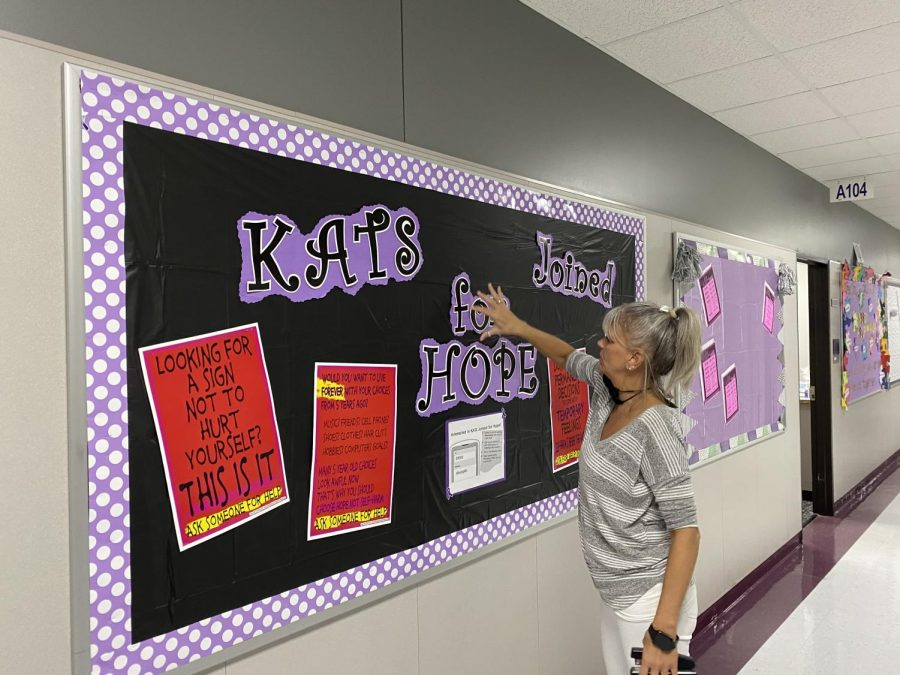 A MESSAGE OF HOPE. Completing a bulletin board advertising the club Kats Joined for Hope, social studies teacher Andrea Eisinger straightens letters on the board.