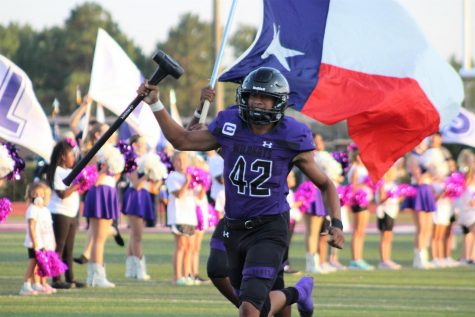 BLEEDING RED, WHITE, BLUE AND PURPLE. As they get super pumped for the game, senior David Sariano runs across the field with a flag and sledge hammer. Soriano is one of five seniors who were elected captains by their team. Sophomore DJ Lagway is also a captain of the team.