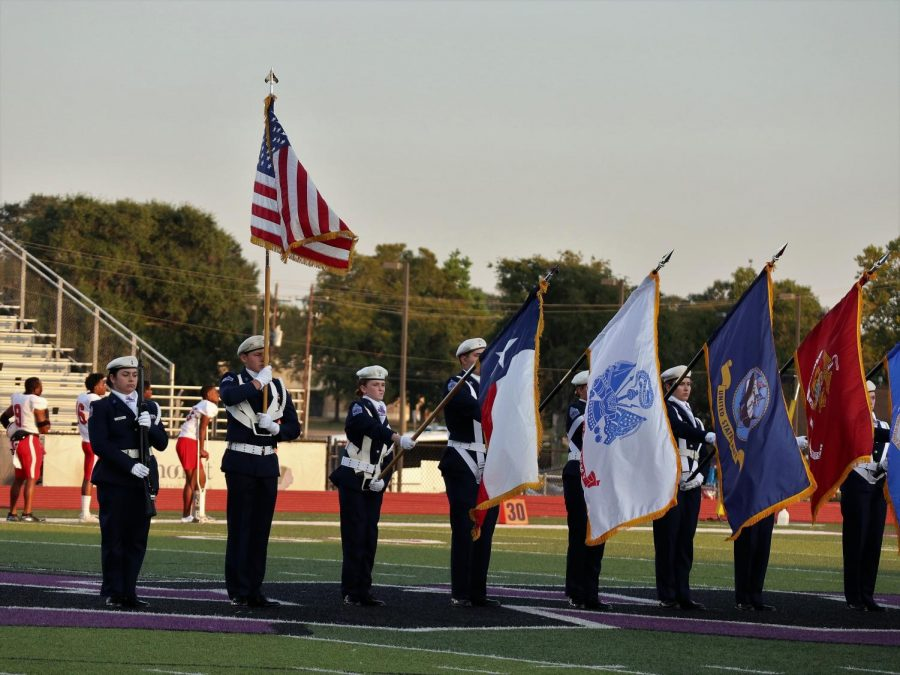 STARS AND STRIPES. Members of AFJROTC present the flag before the game. The organization participates in the pregame activities and posts the flags near the field house.