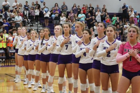 UNITED. Before the match against New Caney, members of the varsity volleyball team unite as the national anthem is played. The team swept the Lady Eagles in three sets.