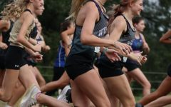 JUST GETTING STARTED. As the varsity girls' race begins, sophomore Kinley Gibbs starts with her teammates. Gibbs was unable to finish the race because of a knee injury and being overheated.
