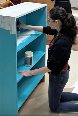 HELPING HANDS.  A member of Mrs. Hornes child development class helps paint a bookshelf at AR Turner. The group now goes to Roark Elementary School this semester to help with students at the school .