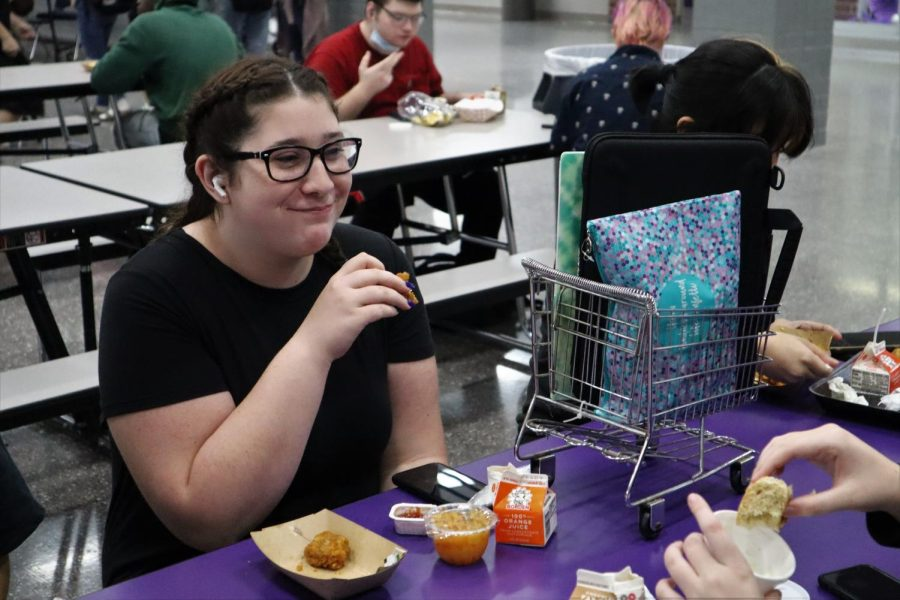 BASKET CASE. Using a small basket that looks like a grocery cart to store her computer and books, sophomore Kynzie Berryman eats lunch on Anything but a Backpack Day.